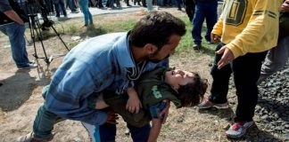 A refugee desperately looking for help for an ill child in Hungary. Photo: Taken from the web independent.ie